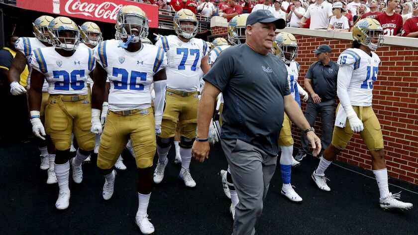 UCLA coach Chip Kelly leads his Bruins on the field before a game.