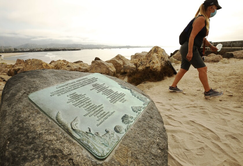 A woman walks on a beach past a boulder with a plaque on it