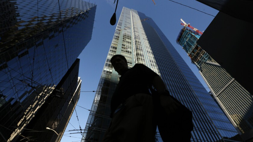 A pedestrian walks past the luxury Millennium Tower, a 58-story high-rise in San Francisco.