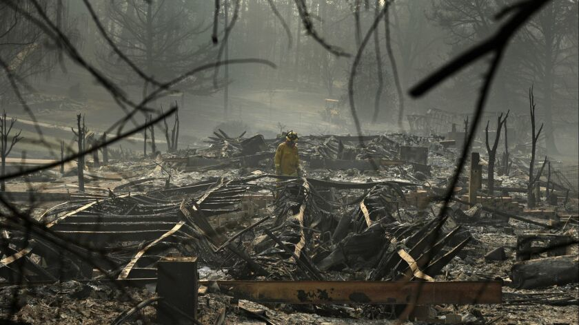 A firefighter searches for human remains in a trailer park destroyed in the Camp Fire, Friday, Nov.