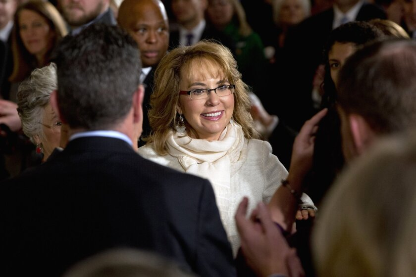 FILE - In this Jan. 5, 2016, file photo, people applaud former Arizona Rep. Gabby Giffords as she arrives in the East Room of the White House in Washington, to hear President Obama speak about steps his administration is taking to reduce gun violence. An official said Thursday, March 24, 2016, a lawsuit filed in the name of the man who shot former U.S. Congresswoman Giffords is bogus. Cosme Lopez with the U.S. Attorney's Office District of Arizona says attorneys for convicted killer Jared Lee Loughner notified the court that Loughner didn't file or authorize the lawsuit. (AP Photo/Jacquelyn Martin, File)