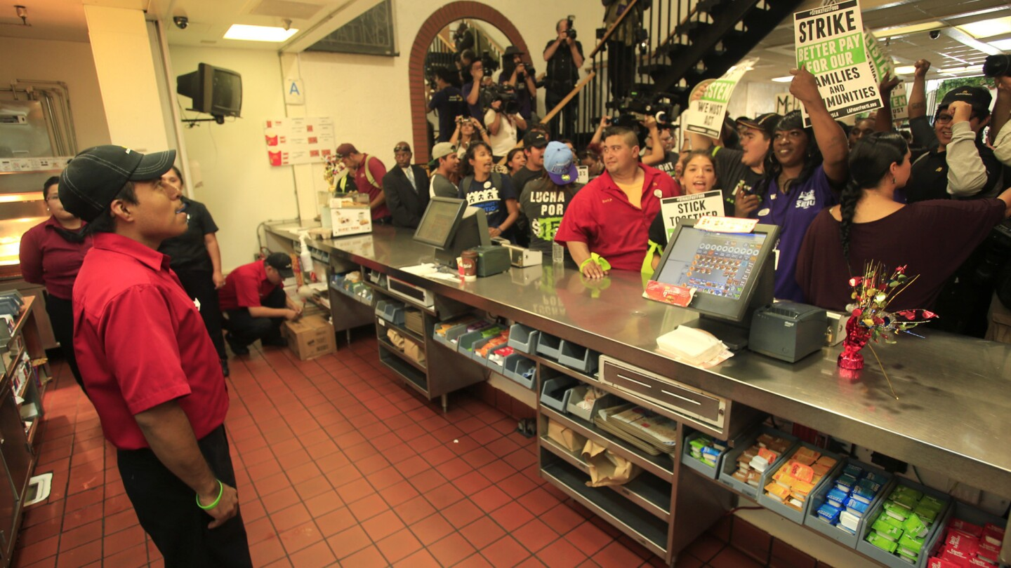 Fast-food workers are joined by supporters Thursday as they walk into a downtown Los Angeles McDonald's in a peaceful demonstration demanding higher wages. Ten protesters were arrested later after sitting in the middle of Broadway.