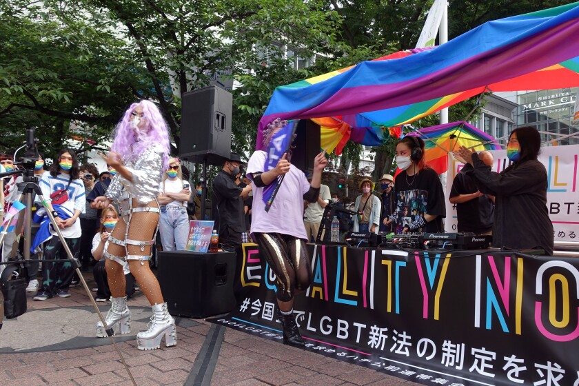 Dozens of LGBTQ activists and supporters of equal rights laws gather at the Shibuya district Sunday June 6, 2021, in Tokyo. Dozens of sexual minority activists and supporters rallied for equal rights outside a main Tokyo station Sunday in an effort to gain public support to get their long-sought equality law enacted before the Olympics amid thinning hope because of the conservative governing party's resistance. (AP Photo/Mari Yamaguchi)
