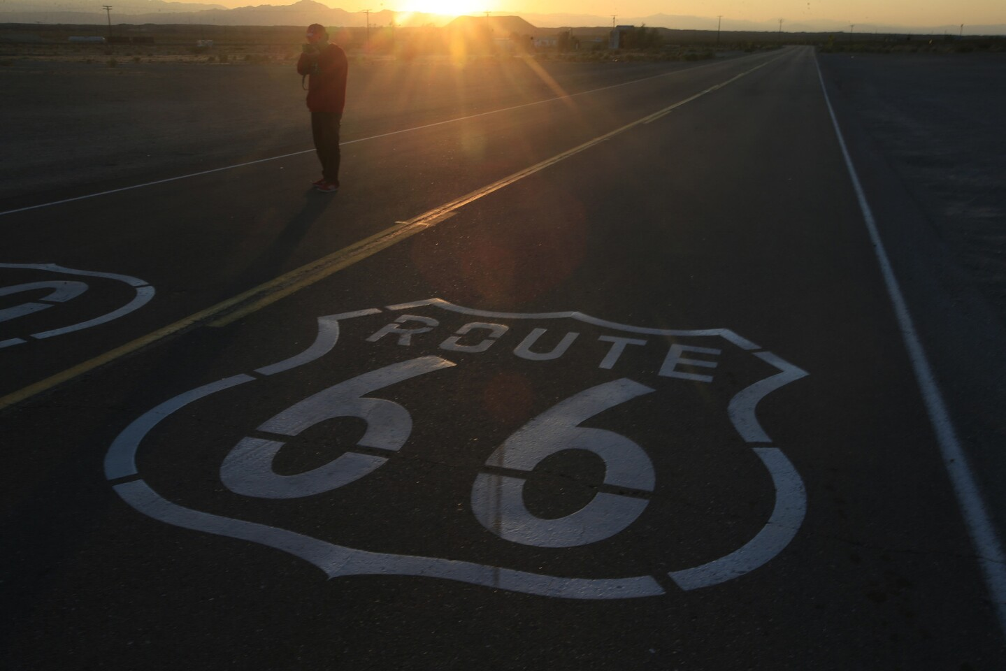 Countless tourists stop for photos of the Route 66 sign painted on the highway in Amboy, Calif.