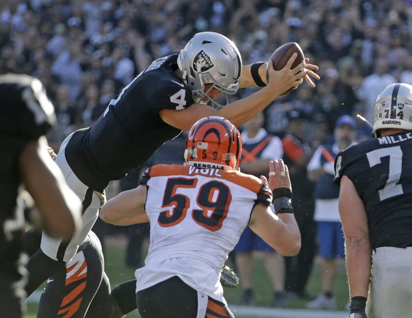 Raiders quarterback Derek Carr leaps across the goal line to score a three-yard touchdown against the Bengals on Nov. 17, 2019, in Oakland.