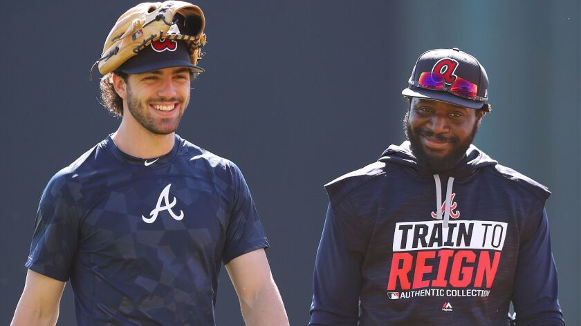 Braves infielders Dansby Swanson, left, and Brandon Phillips share a laugh as they wrap up a day of spring training practice at Champion Stadium on Friday, Feb. 17, 2017, at the ESPN Wide World of Sports in Lake Buena Vista, Fla.