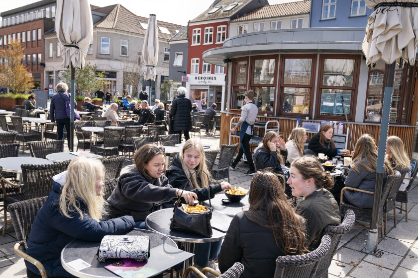 FILE - In this Wednesday April 21, 2021 file photo, people sit outside a restaurant for outdoor service in Roskilde Denmark, as cafes and bars reopened. After 548 days with restrictions to limit the spread of COVID-19, Denmark's high vaccination rate has enabled the Scandinavian country to become one of the first European Union nations to lift all domestic restrictions. The return to normality has been gradual, but as of Friday Sept. 10, 2021, the digital pass — a proof of having been vaccinated — is no longer required when entering night clubs, making it the last virus safeguard to fall. (Claus Bech/Ritzau Scanpix via AP, File)