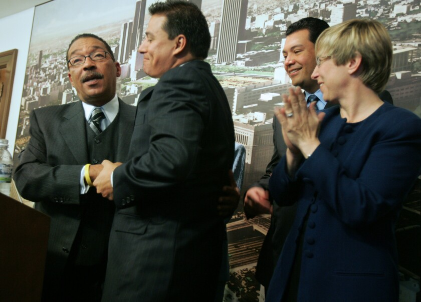 Los Angeles City Council members-elect Herb Wesson, left and Jose Huizar embrace at a news conference at City Hall before a session in 2005.
