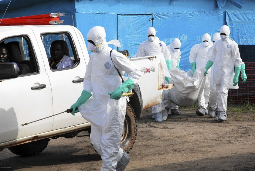 Liberian health workers carry the body of an ebola victim in Foya. The World Health Organization says nearly 730 people have died there and in neighboring Guinea and Sierra Leone since February.