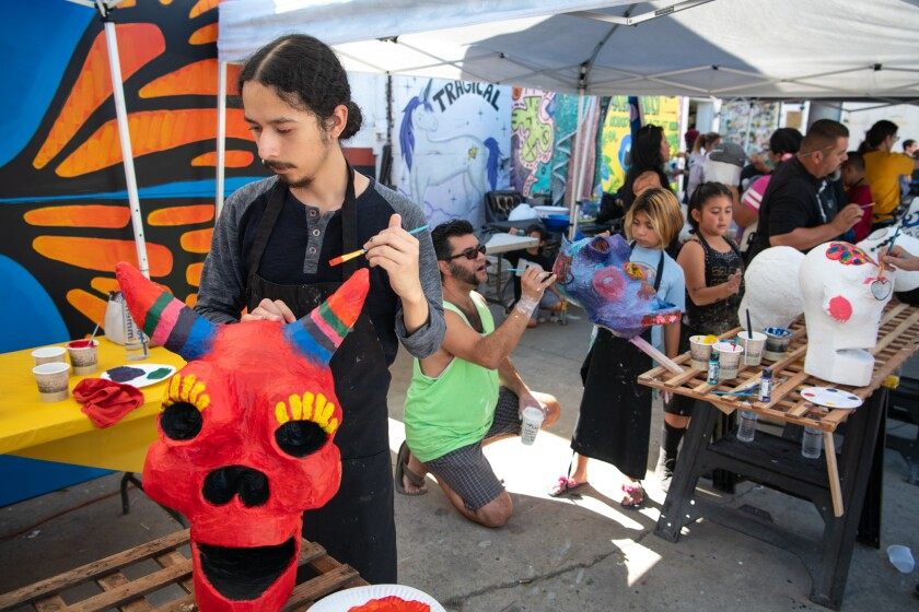 Steve Vazquez, left, paints a paper mache skull for Day of the Dead at Self Help Graphics & Art.