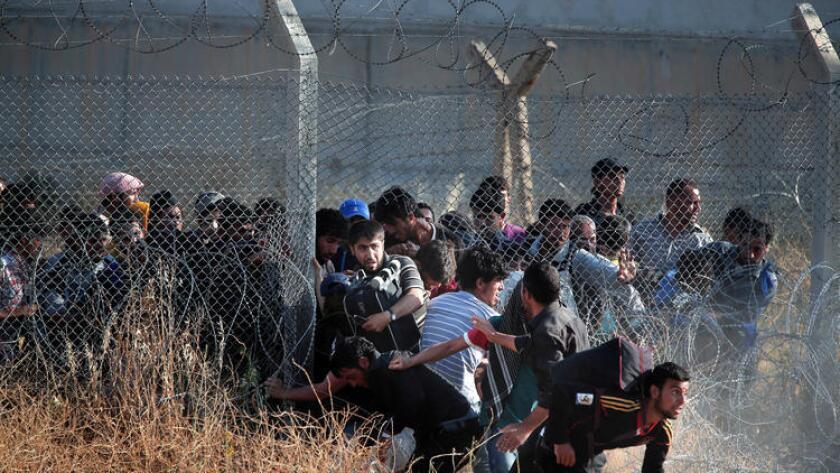 Refugiados sirios irrumpen en Turquía luego de romper una valla en la frontera, el 14 de junio de 2015. En años recientes, Turquía ha construido un muro de concreto en ciertas zonas de la frontera.