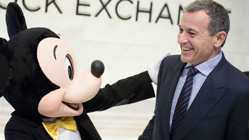 Mickey Mouse and Robert Iger, chief executive of Walt Disney Co., stand together before ringing the opening bell of the New York Stock Exchange on Nov. 27.