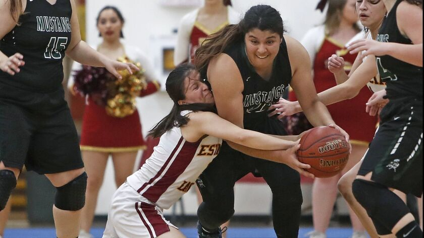 Costa Mesa High's Katie Belmontes, right, is fouled by Estancia's Cielo Cruz as the Eagles turn the