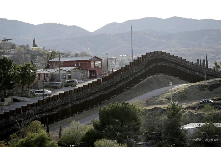 Valla fronteriza reforzada con un tendido doble de alambre de navajas separa a Nogales, México (i) de Nogales, Arizona.