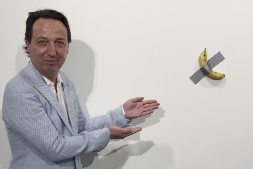 """In this Dec. 4, 2019 photo, gallery owner Emmanuel Perrotin poses next to Maurizio Cattlelan's """"Comedian"""" at the Art Basel exhibition in Miami Beach, Fla. The work sold for $120,000. (AP Photo/Siobhan Morrissey)"""