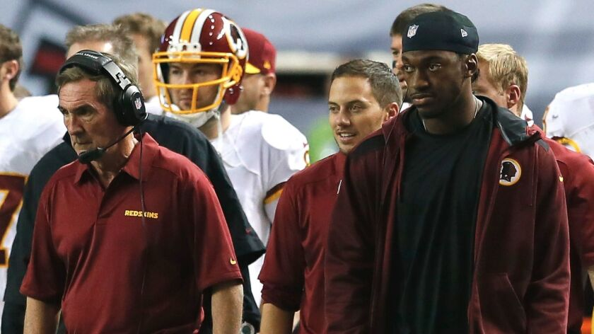 Mike Shanahan, left, and Robert Griffin III watch from the Washington Redskins' sideline on Dec. 15, 2013.