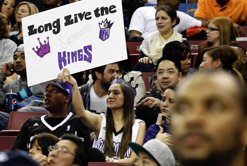 A fan holds up a sign at a Kings game, expressing her hope that the team doesn't leave Sacramento. The owners have reportedly reached an agreement to sell the team to a Seattle investment group.