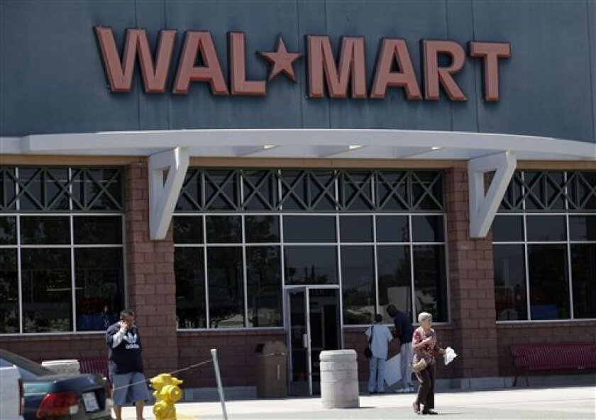 People pass in front of a Wal-Mart store in San Diego, Monday, May 3, 2010. Wal-Mart Stores Inc. has agreed to pay $27.6 million to settle allegations that it improperly handled and dumped hazardous waste at stores across California, prosecutors said Monday. (AP Photo/Gregory Bull)