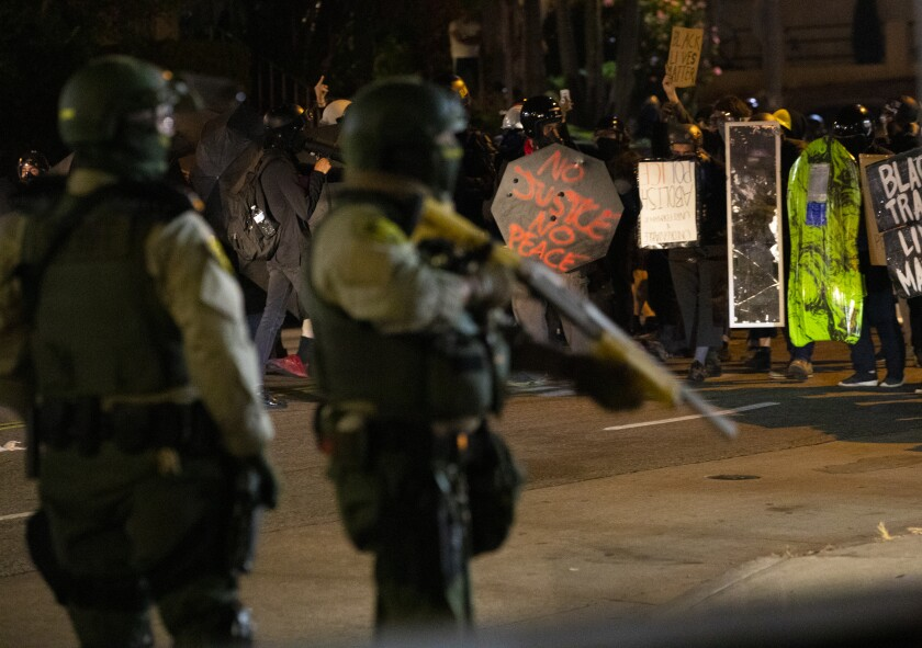 Los Angeles County sheriff's deputies watch a crowd of protesters.