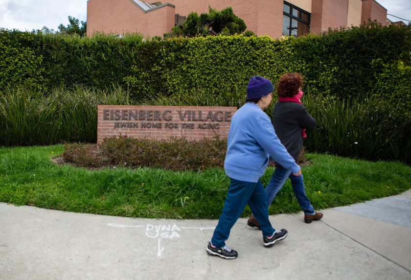 People walk past Eisenberg Village nursing home where they are screening all incoming for symptoms of the coronavirus in Reseda.