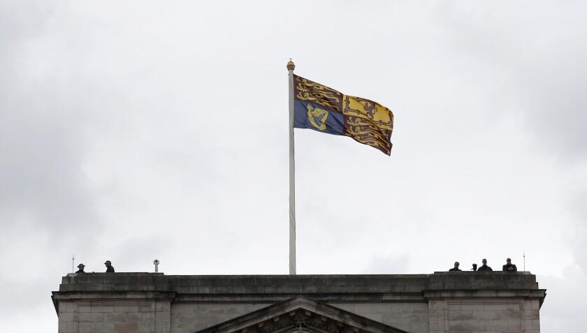 Agentes de policía observan desde el tejado del Palacio de Buckingham antes de que la reina Isabel II salga de palacio