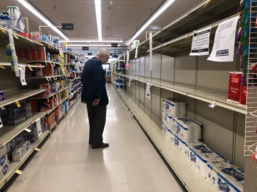 A man looks at nearly empty shelves of toilet paper at a Vons in April