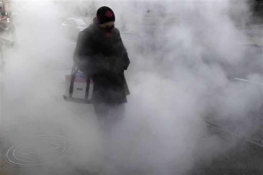 A person bundled up against the cold passes through steam rising from a manhole cover in Philadelphia, Friday, Jan. 16, 2009. (AP Photo/Matt Rourke)