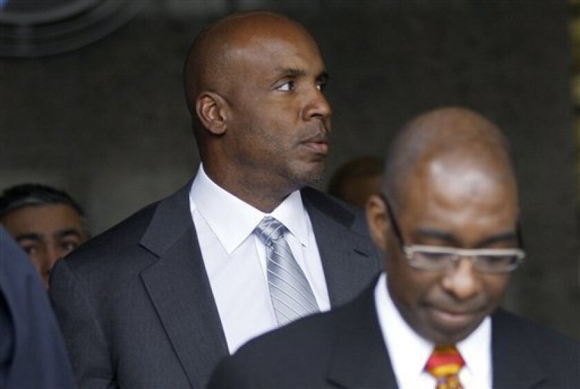 Former baseball player Barry Bonds, left, leaves federal court in San Francisco, Tuesday, April 5, 2011. Prosecutors rested their case against Bonds in his perjury trial Tuesday. (AP Photo/Jeff Chiu)