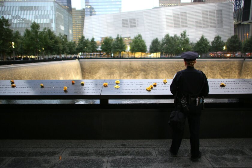 Port Authority Police Officer Donna Przybyszewski reflects on the colleagues she knew who lost their lives during the attacks of Sept. 11, 2001, at the South Tower Memorial Pool before memorial observances held at the site of the World Trade Center in New York, Thursday, Sept. 11, 2014. (AP Photo/T