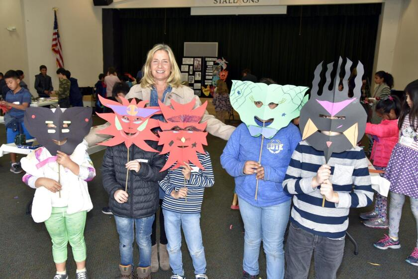 Principal Peg LaRose and students displaying their masks made with help of the San Diego Guild Of Puppetry