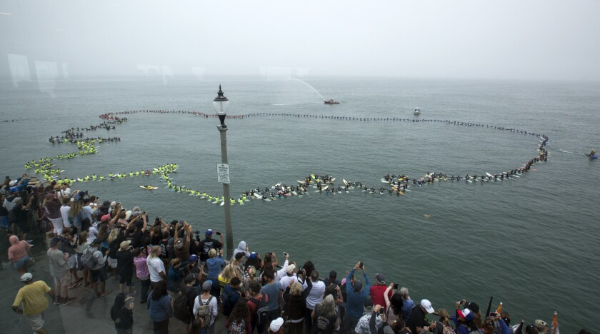 More than 500 surfers gather for a record-breaking paddle out off the Huntington Beach pier to promo