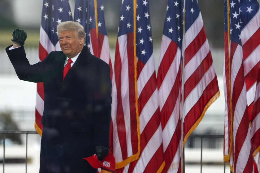 Donald Trump raises his fist as he stands in front of U.S. flags.