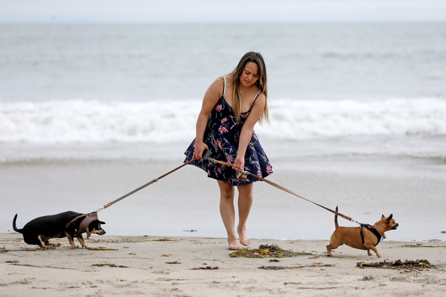 "VENTURA, CA -- MAY 28: Mary Jasso-Brooks, of Ventura, with James, left, and Paige, walk along the surf at the beach on Thursday, May 28, 2020, in Ventura, CA. While many parks and beaches in Ventura County have been open for active use for weeks, Ventura city officials will begin to further ease restrictions at their outdoor spaces starting Friday. ""Passive"" activities such as sitting and sunbathing will be allowed ""as long as the public maintains a safe physical distance of six feet and avoids congregating in large groups. (Gary Coronado / Los Angeles Times)"
