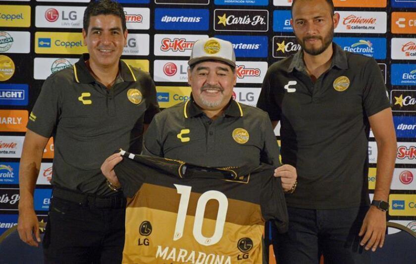 El argentino Diego Armando Maradona (c) muestra una camiseta del equipo Dorados de Culiacán durante una rueda de prensa hoy, lunes 10 de septiembre de 2018, en la ciudad de Culiacán, estado de Sinaloa (México). EFE