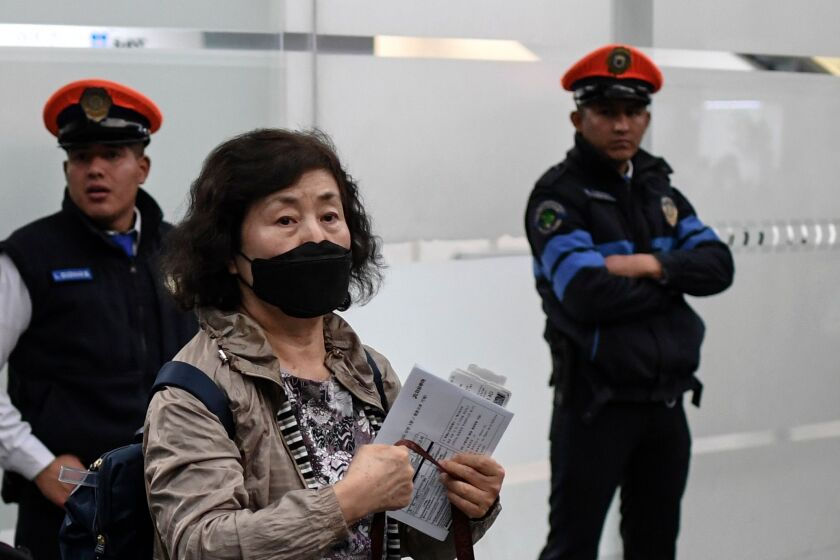 Woman wears a protective mask at Mexico City International Airport