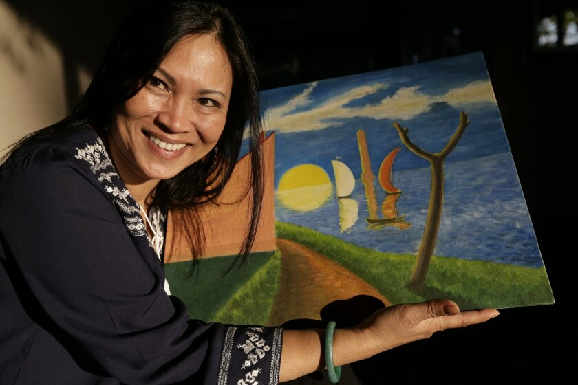 Erika Colligan poses with a painting made by her father Tuesday, Jan. 12, 2016, in San Diego. After three decades searching for her father's artwork - paintings the South Vietnam pilot made for the U.S. Air Force aviators who trained him during the Vietnam war, Colligan recently found one. The pain