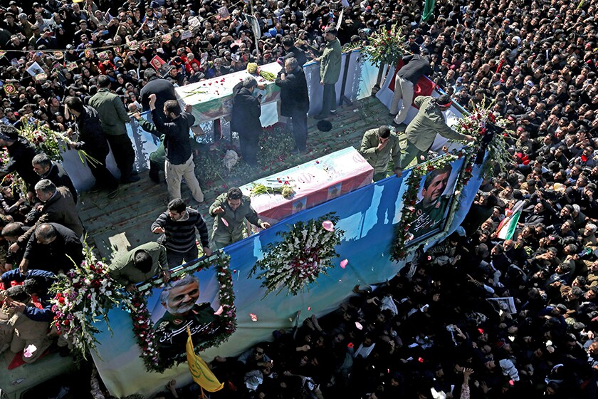 Mourners gather around a vehicle carrying the coffin of Gen. Qassem Suleimani.