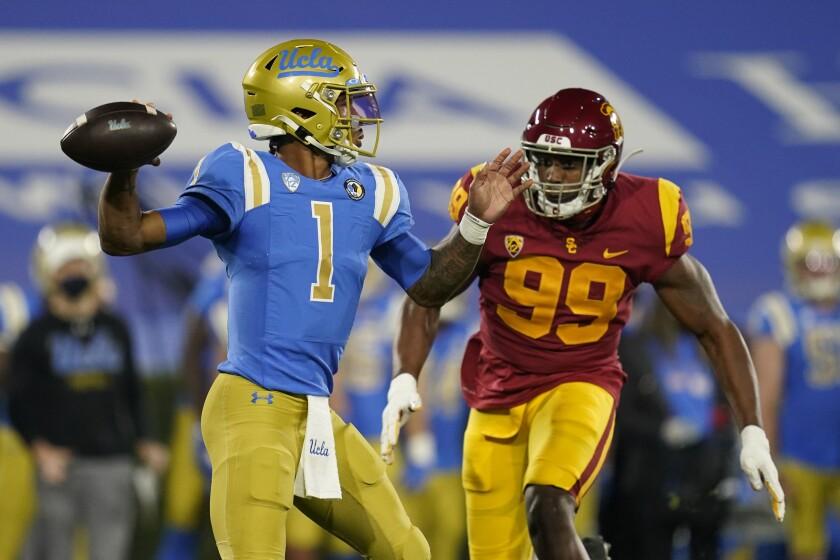 A USC football player runs toward the UCLA quarterback as he prepares to pass.