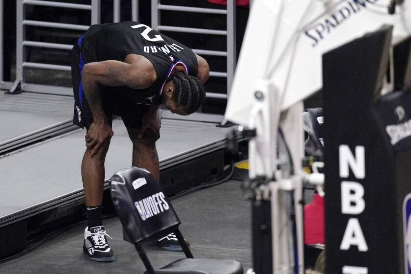 Los Angeles Clippers forward Kawhi Leonard holds his knee after stepping awkwardly during the second half in Game 4 of a second-round NBA basketball playoff series against the Utah Jazz Monday, June 14, 2021, in Los Angeles. (AP Photo/Mark J. Terrill)