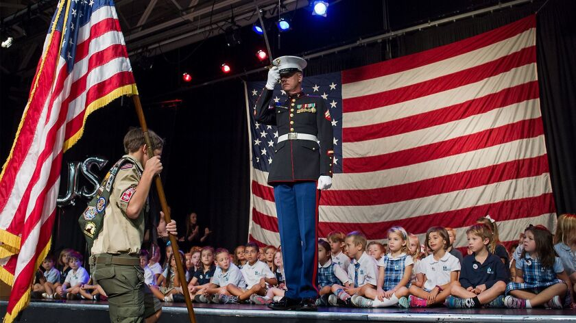 Retired U.S. Marine Dwight Hanson salutes as Boy Scout Sam Perkins carries the U.S. flag during a Veterans Day commemoration at Mariners Christian School in Costa Mesa on Nov. 11, 2016.