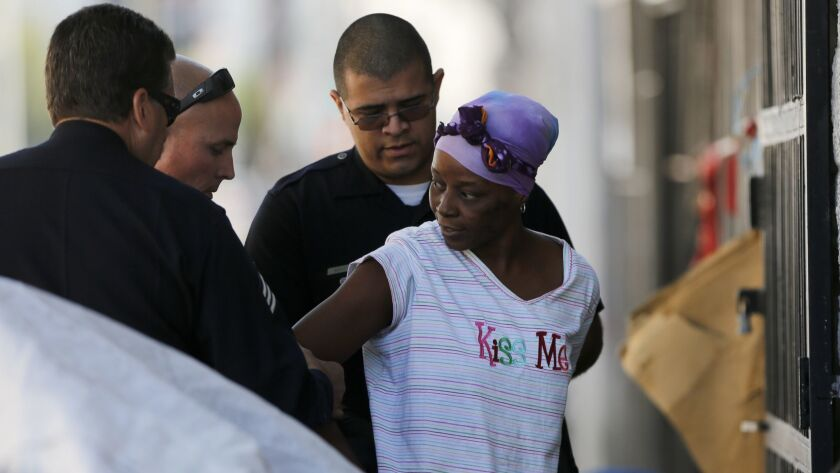 A homeless resident living along 5th Street is arrested on skid row during a cleanup.