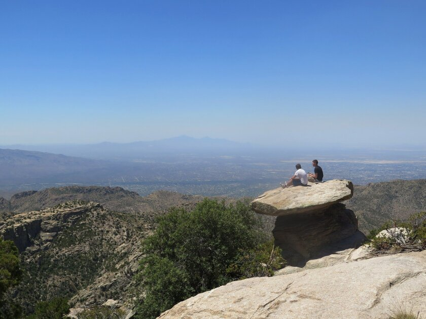 In this Friday, June 3, 2016 photo at Mount Lemmon, just north of Tucson, Ariz., students sit on a large rock overlooking the landscape. Many in Tucson escape to Mount Lemmon as temperatures rise to triple-digits, heading warnings of excessive heat. Mount Lemmon is the highest point in the Santa Ca
