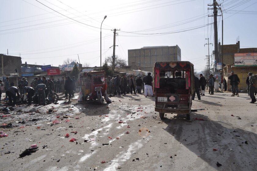 Afghan security officials inspect the scene of a suicide bomb attack in Meymaneh, Afghanistan.