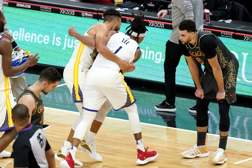 Golden State Warriors guard Damion Lee (1) celebrates with Stephen Curry as Chicago Bulls guard Zach LaVine, right, reacts after the Warriors defeated the Bulls 129-128 in an NBA basketball game in Chicago, Sunday, Dec. 27, 2020. (AP Photo/Nam Y. Huh)