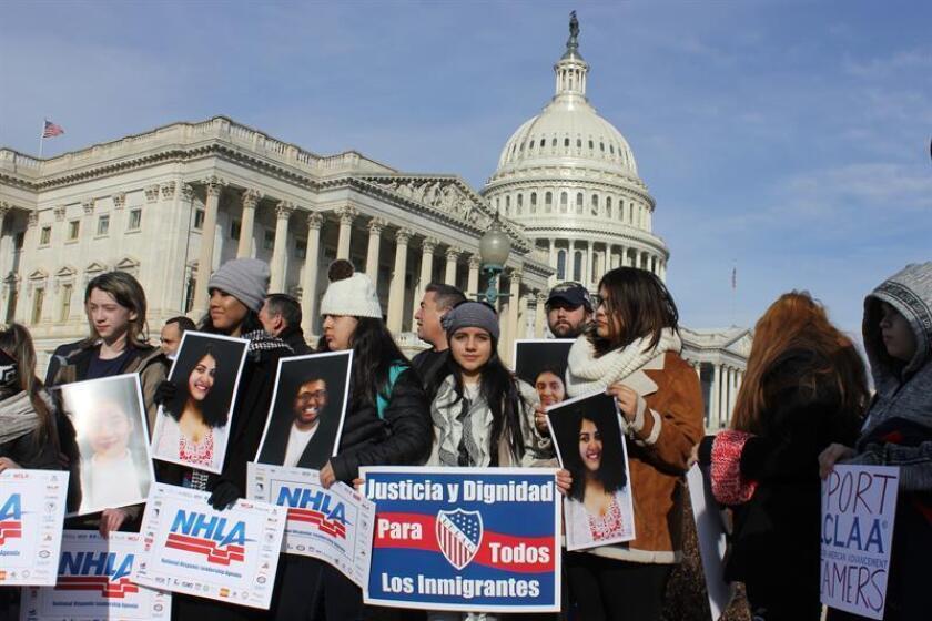 """Varios jóvenes sostienen pancartas que reivindican """"Justicia y dignidad para todos los inmigrantes"""" y otras con nombre de la coalición Agenda Nacional de Liderazgo Hispano (NHLA), durante una protesta a favor de los jóvenes beneficiados con el programa de Acción Diferida para los Llegados en la Infancia (DACA) hoy, viernes 19 de enero de 2018, frente al Capitolio nacional en Washington, DC (EE.UU.). Una coalición formada por las 45 organizaciones latinas más importantes del país pidió hoy al Congreso poner fin a los """"juegos políticos"""" y encontrar una solución """"inmediata y permanente"""" para los """"soñadores"""", los jóvenes indocumentados llegados a EE.UU. durante la infancia. EFE"""