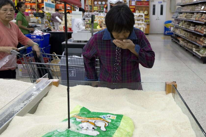 In this Wednesday, Nov. 11, 2015, photo, a woman smells rice on sale at a Wal-Mart in Shenzhen, in southern China's Guangdong province. If Arkansas-based Wal-Mart wants to win over foreign consumers, it has to shed some of its American ways, and cater to very different customs and conventions. China is the ultimate prize. (AP Photo/Ng Han Guan)