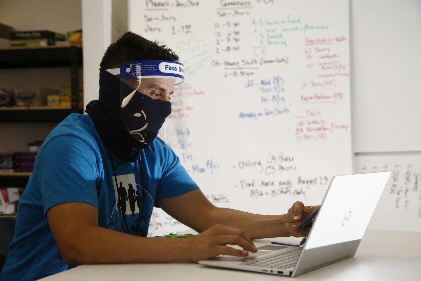 Wearing a face covering and face shield while working amid the coronavirus, Maico Olivares, lead voter registration organizer for Central Arizonans for a Sustainable Economy, works his phone and computer as he tries to reach about 25 people a day, mostly within the Latino community, to persuade them to register to vote Thursday, Aug. 6, 2020, in Phoenix. Like others who register people to vote, those efforts have become extremely difficult during the pandemic. (AP Photo/Ross D. Franklin)