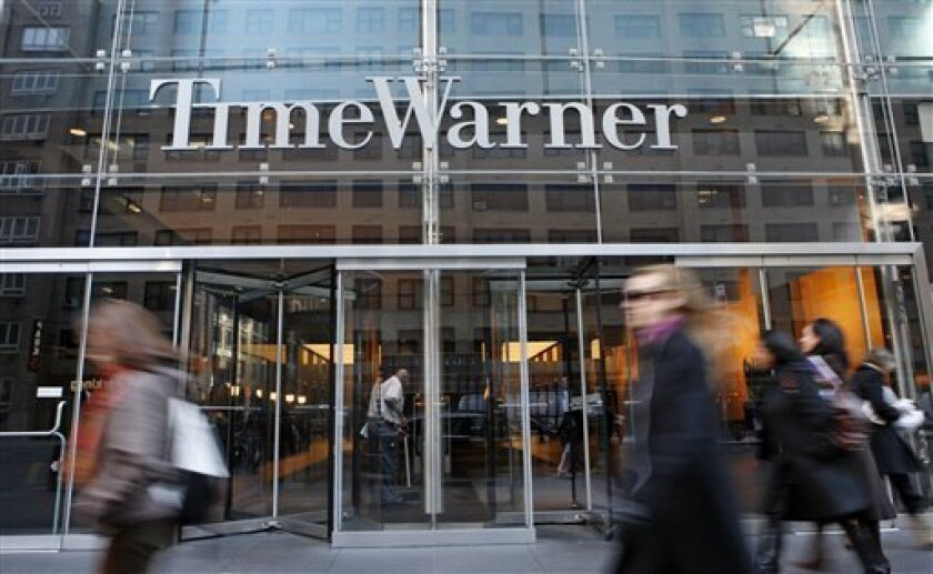 FILE - In this Nov. 7, 2007 file photo, people walk by the Time Warner building in New York. Media conglomerate Time Warner Inc. reported a 38 percent drop in third-quarter profit on Wednesday, Nov. 4, 2009, hurt by declines at its AOL and publishing segments.(AP Photo/Diane Bondareff, file)