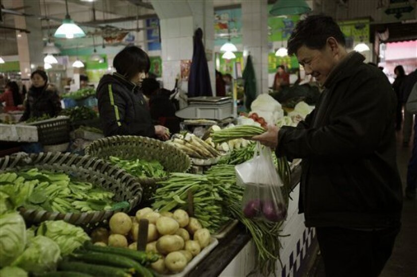 In this March 20, 2012 photo, a customer buys vegetable from a market in Shanghai, China. China's inflation edged up in March as the government shifted focus from containing politically dangerous price rises to stimulating its slowing economy. Consumer prices rose 3.6 percent over a year earlier, up from February's 3.2 percent, data showed Monday, April 9, 2012. (AP Photo/Eugene Hoshiko)