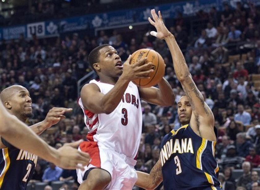 Toronto Raptors guard Kyle Lowry, centre, drives to the net past Indiana Pacers guard George Hill, right, during first half NBA basketball action in Toronto on Wednesday, Oct. 31, 2012. (AP Photo/The Canadian Press, Nathan Denette)